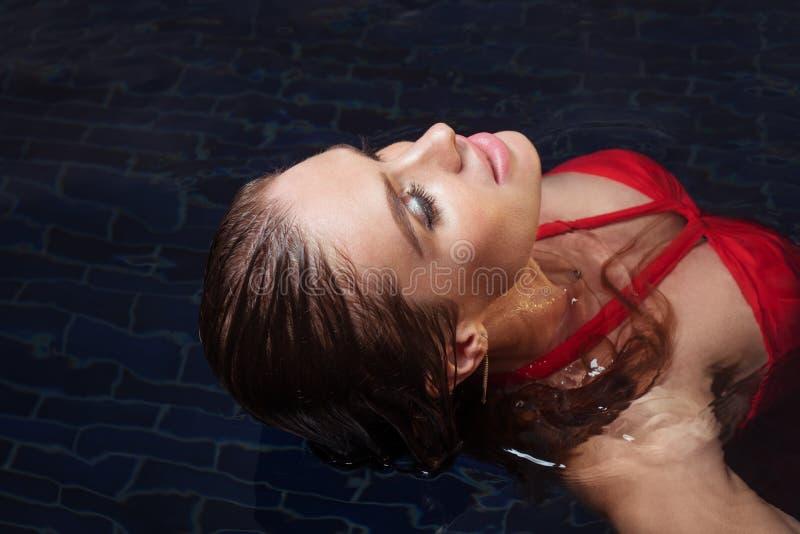 Женщина красоты в красном платье в бассейне стоковая фотография