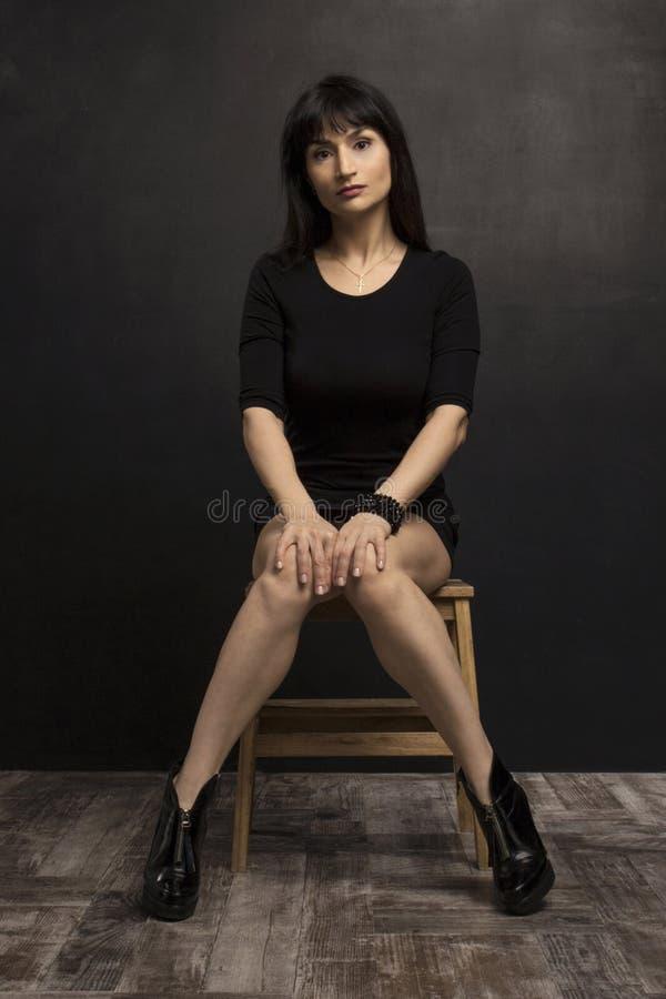Женщина красоты в черном коротком платье на стуле перед темной стеной стоковые фото