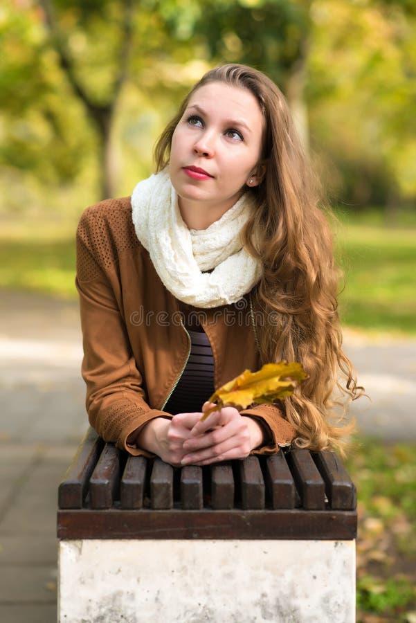 Женщина красоты держа листья осени и ослабляя стенд стоковое фото rf
