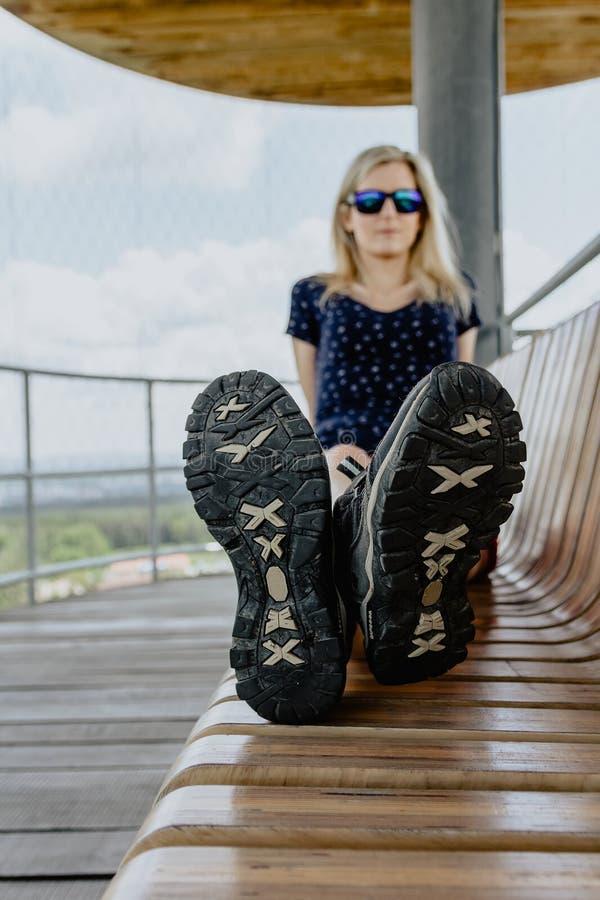 Женщина красоты молодая кавказская белокурая сидит на стенде, фокусе к ботинкам стоковая фотография