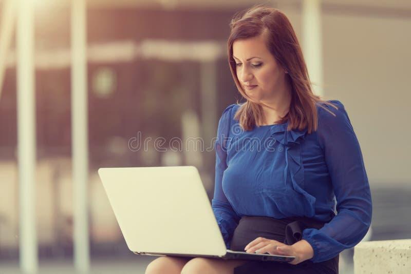 Женщина красоты сидя и используя ноутбук стоковая фотография rf