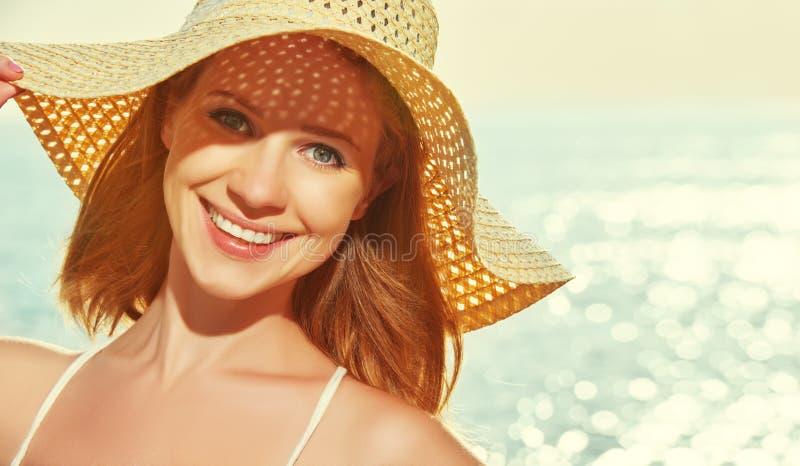 Женщина красоты счастливая в шляпе наслаждается морем на заходе солнца на пляже стоковое изображение rf