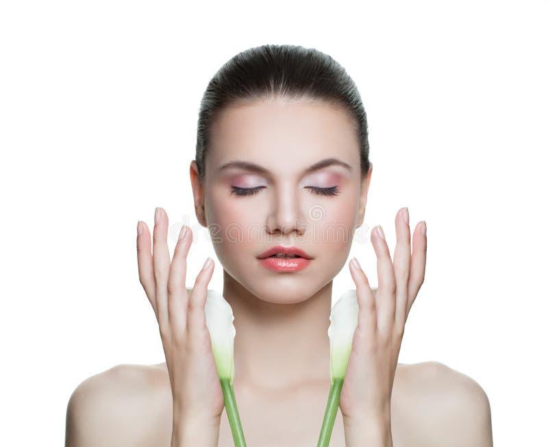 Женщина красоты с ясным здоровым цветком кожи и лилии изолированным на белизне Портрет спа модельный Skincare и лицевая концепция стоковая фотография
