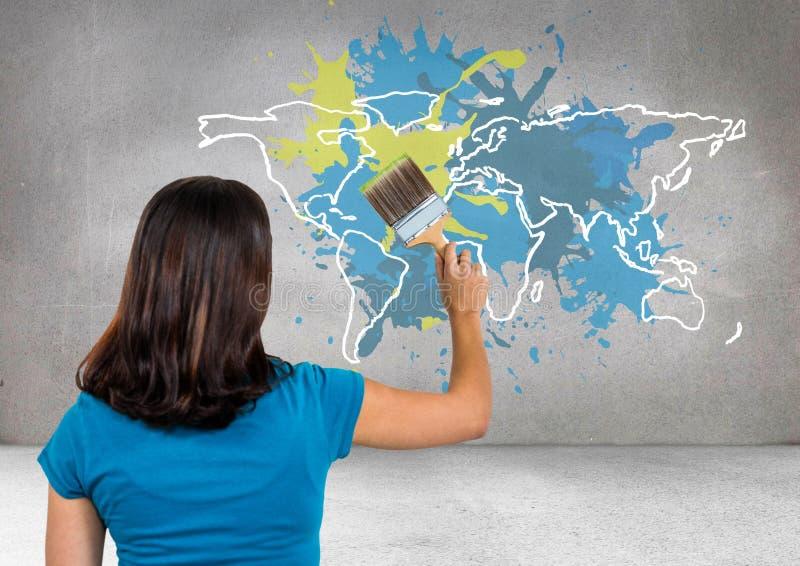 Женщина крася красочную карту с краской splattered предпосылка стены стоковые изображения