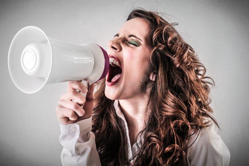 Женщина кричащая через мегафон стоковая фотография