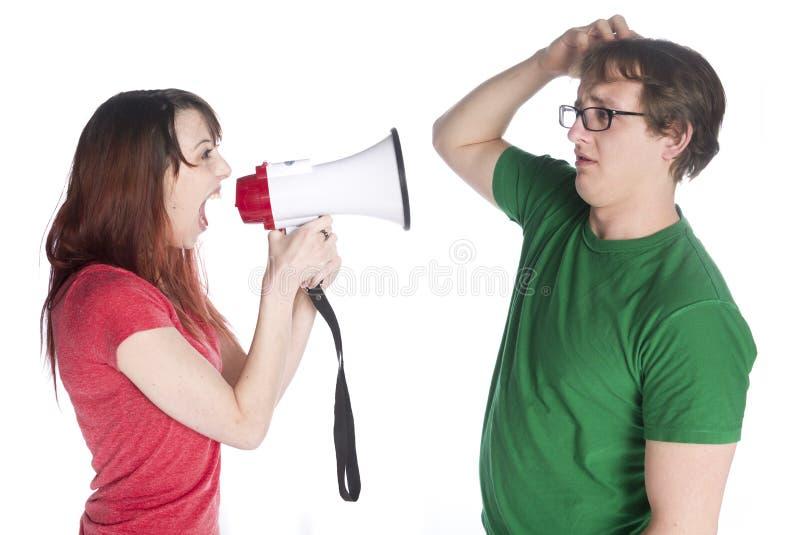 Женщина крича к ее человеку с мегафоном стоковая фотография rf