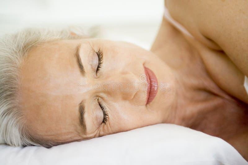 женщина кровати лежа стоковая фотография rf