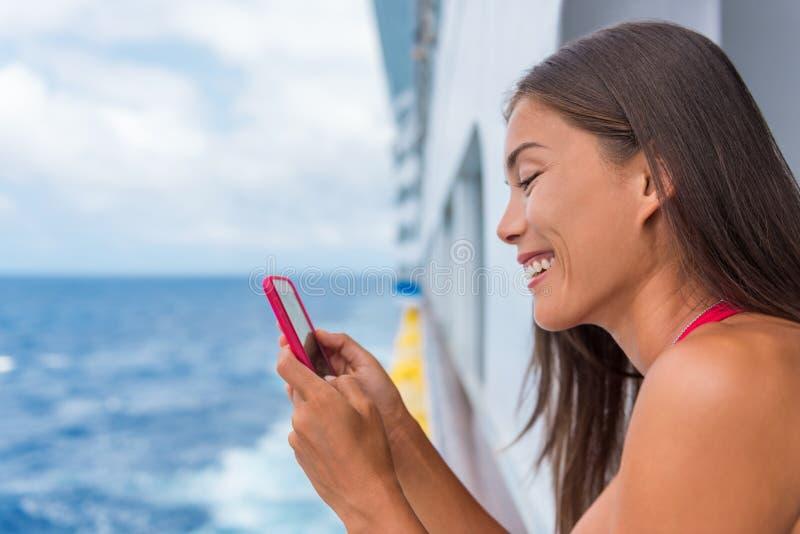 Женщина-круиз-лайнер пользуется мобильным телефоном в отпуске в океане Девушка из Азии пишет смс на wifi в тропические праздники  стоковое изображение rf