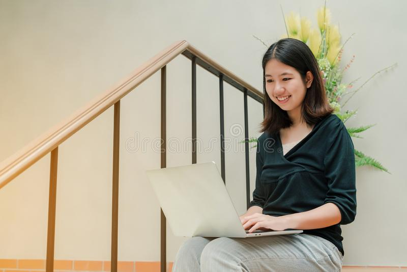Женщина крупного плана азиатская красивая нося черную рубашку сидя в лестницах в доме использует ноутбук для работы счастливой стоковые изображения