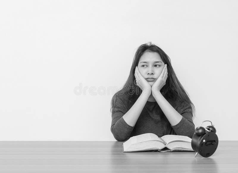 Женщина крупного плана азиатская сидя для прочитала книгу с пробуренной эмоцией и думая сторону на стене деревянной таблицы и бел стоковые изображения rf