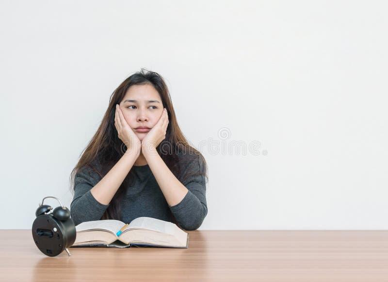 Женщина крупного плана азиатская сидя для прочитала книгу с пробуренной эмоцией и думая сторону на стене деревянной таблицы и бел стоковые фотографии rf