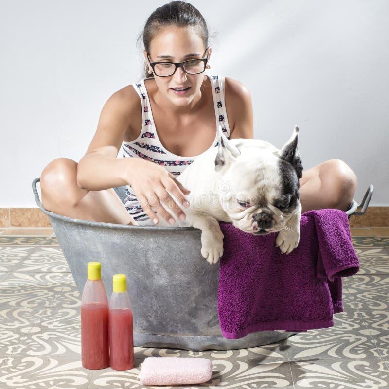 Женщина купая собаку стоковые изображения