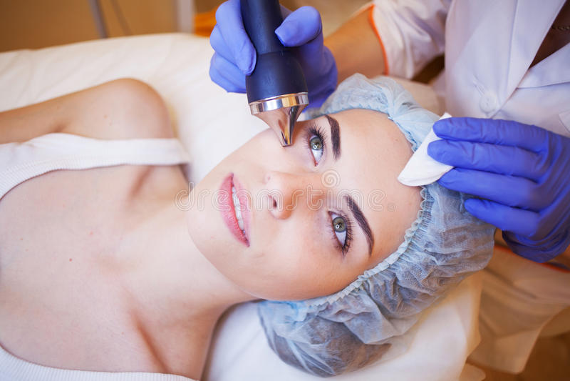 Женщина курорта косметологии делая процедуры на стороне стоковое фото rf