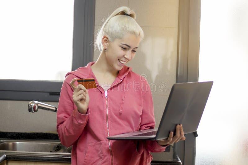Женщина кухни на ПК компьтер-книжки варя делающ еду используя компьютер fo стоковые изображения