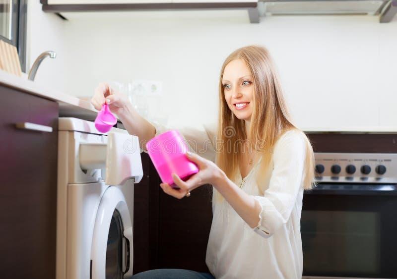 Женщина кладя белитель внутри к стиральной машине стоковое изображение