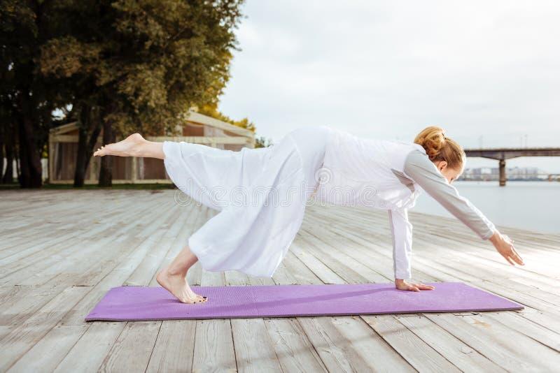 Женщина легко держа баланс пока практикующ представление йоги стоковая фотография
