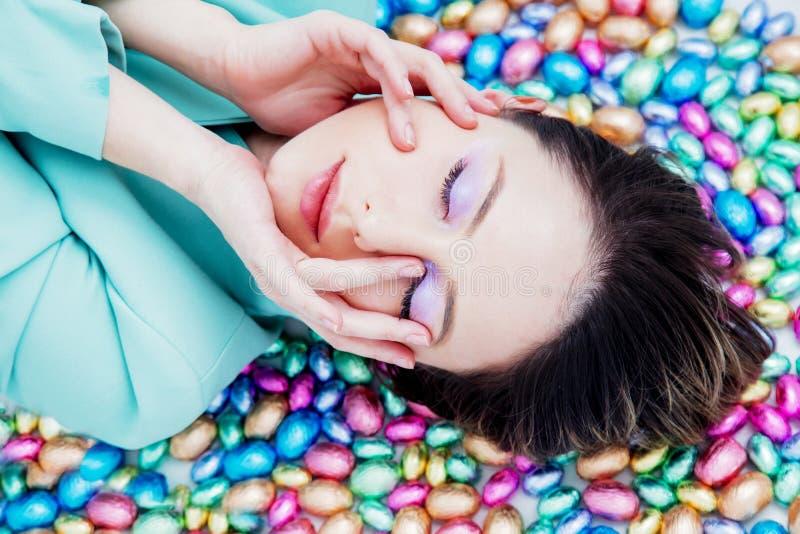 Женщина лежа вниз на пасхальных яйцах шоколада стоковая фотография rf