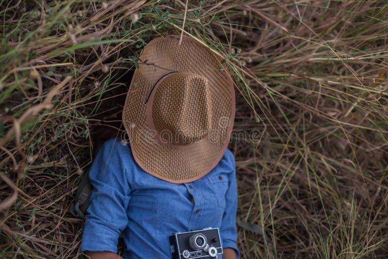 Женщина лежа в парке с камерой и шляпой стоковое фото rf
