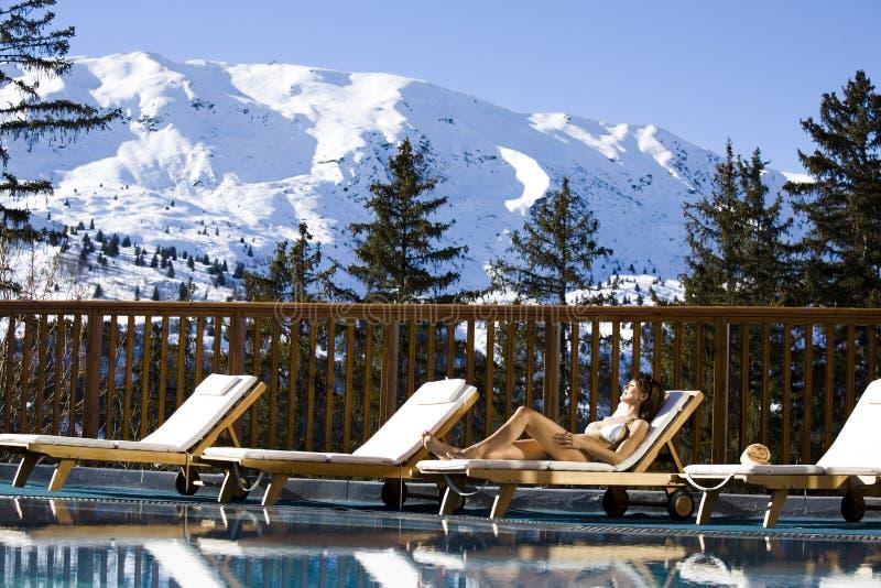 Женщина лежа на бассейне в бикини в снежных горах стоковые фотографии rf