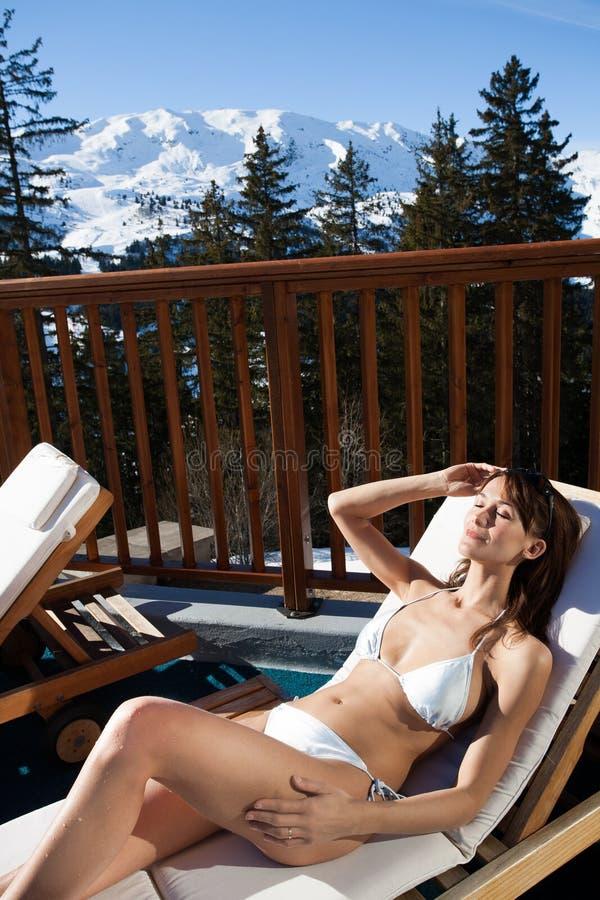 Женщина лежа на бассейне в бикини в снежных горах стоковые фото