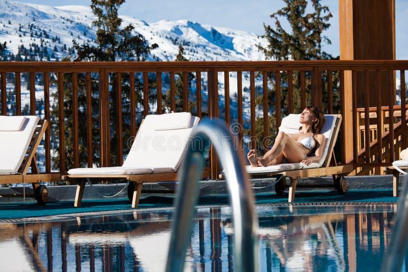 Женщина лежа на бассейне в бикини в снежных горах стоковое изображение