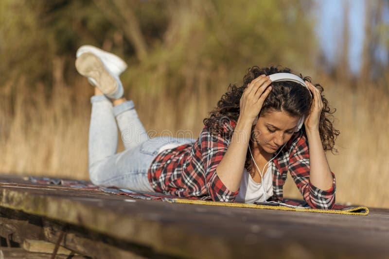 Женщина лежа на доках слушая музыку стоковое фото rf