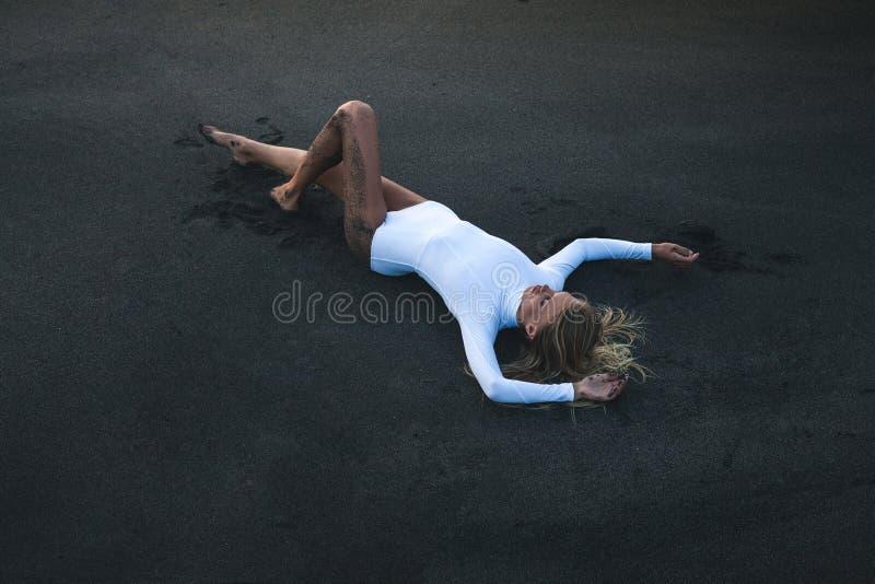 Женщина лежа на песчаном пляже стоковые фотографии rf