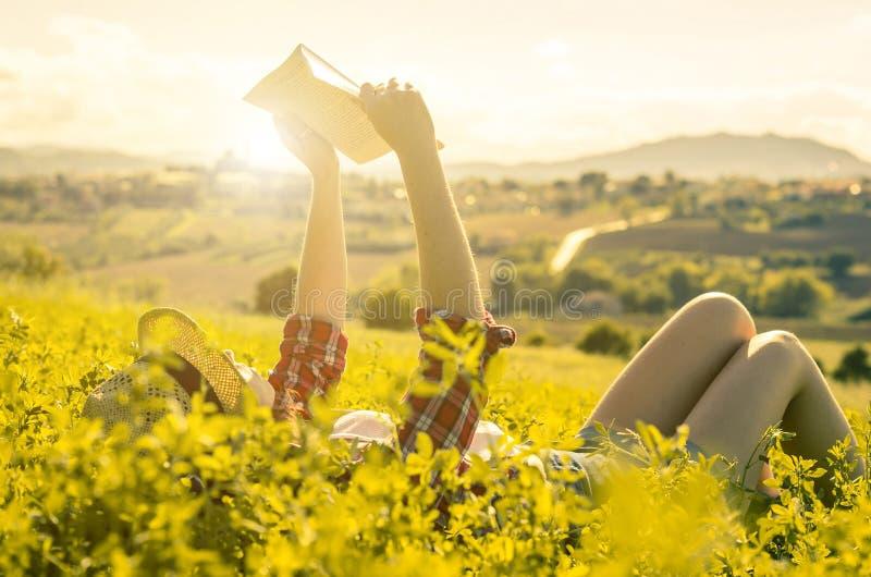Женщина лежа на траве прочитала книгу в сельской местности стоковое фото rf
