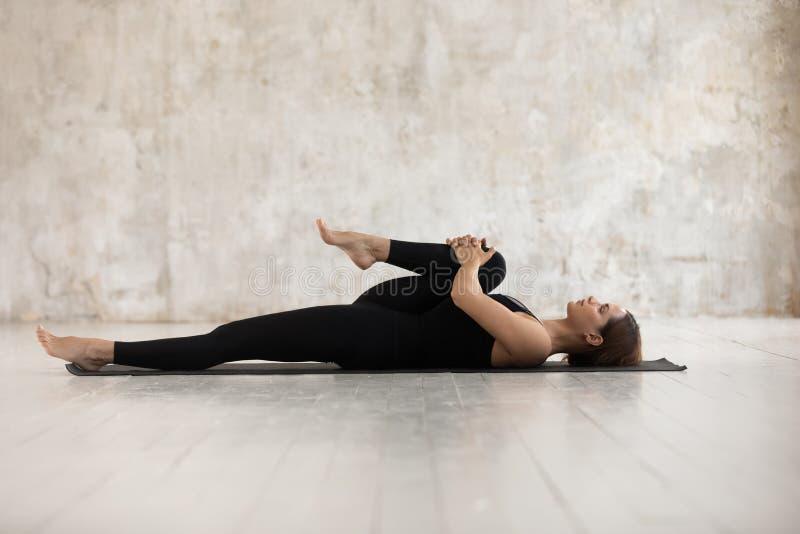 Женщина лежа на циновке делая половинные колени к представлению комода стоковая фотография rf