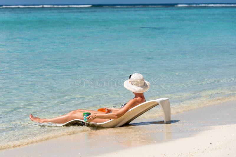 Женщина лежа на deckchair в океане, Мальдивах, Индийском океане Скопируйте космос для текста стоковое изображение rf