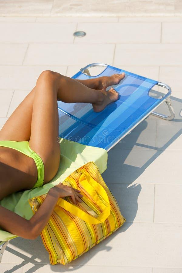 Женщина лежа на deckchair плавательным бассеином стоковая фотография rf