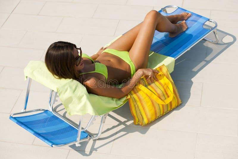 Женщина лежа на deckchair плавательным бассеином стоковое изображение