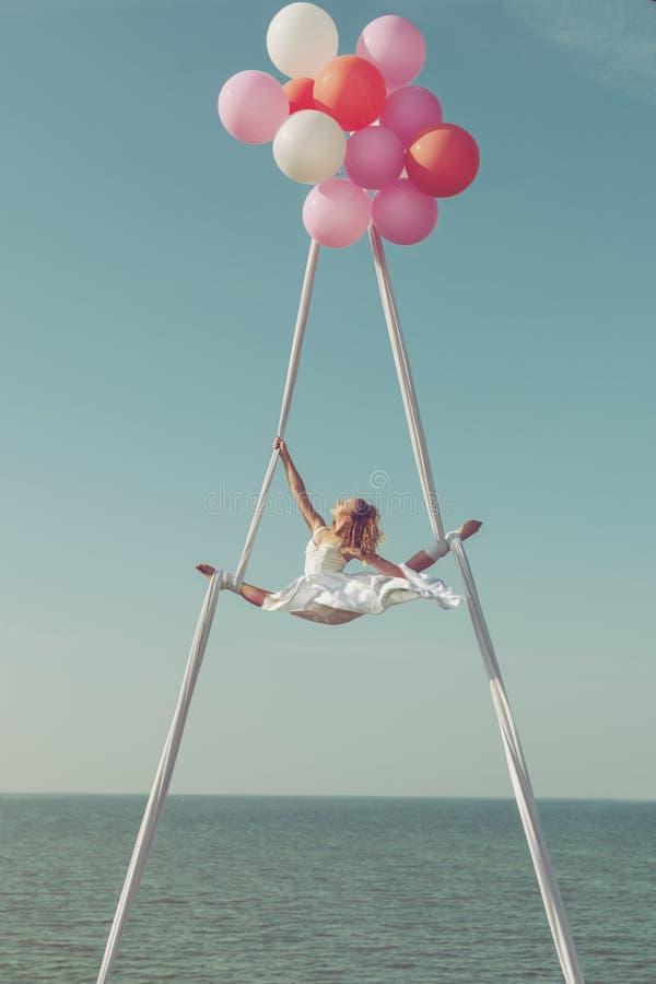 Женщина летает в воздушные шары высоко в небе стоковая фотография