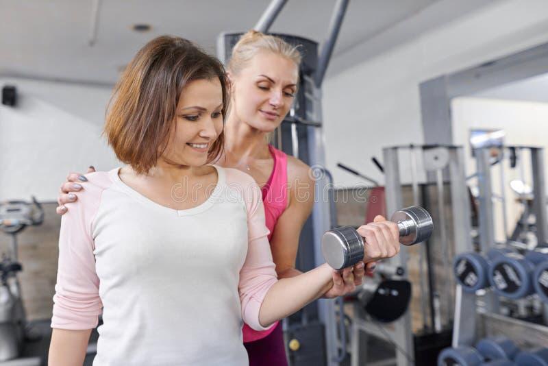Женщина лета личного инструктора фитнеса помогая работая в оздоровительном клубе Концепция возраста спорта фитнеса здоровья стоковые изображения rf