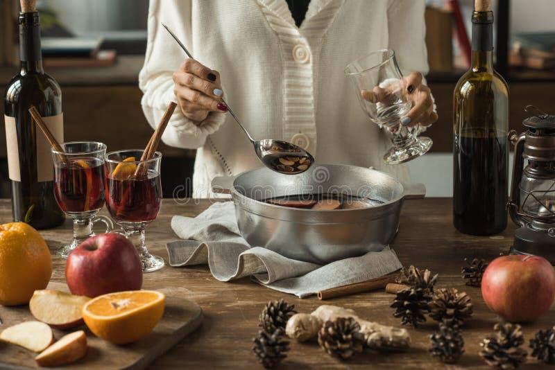 Женщина лить домодельное обдумыванное вино стоковая фотография rf