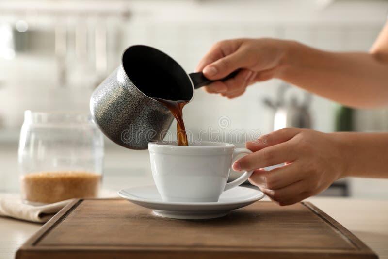 Женщина лить свежий кофе в чашку на таблице в кухне стоковое изображение