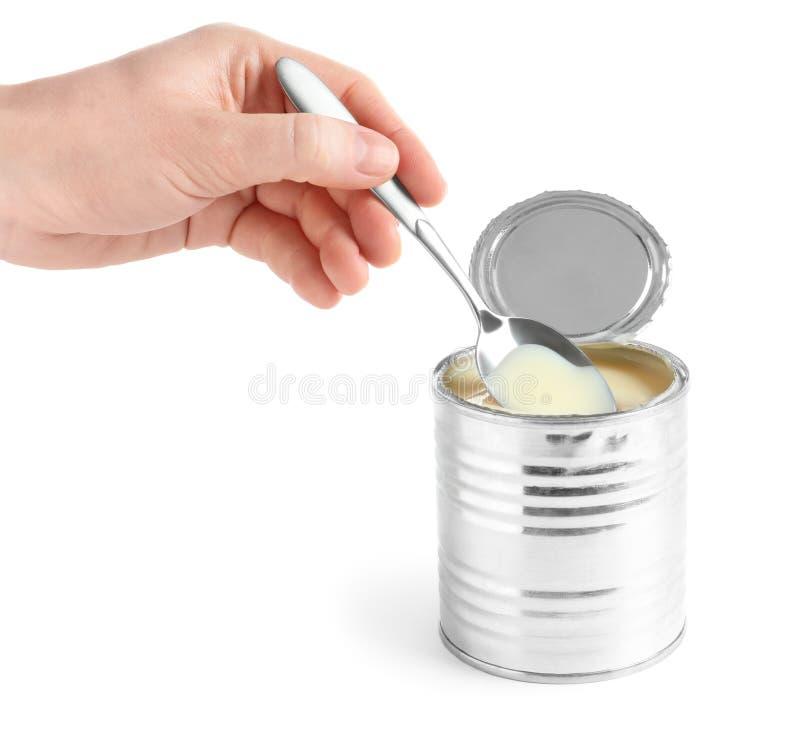 Женщина лить сконденсированное молоко от ложки в жестяную коробку на белой предпосылке, крупном плане стоковые фото