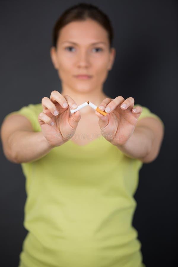 Женщина ломая сигарету решила прекратить курить стоковая фотография rf