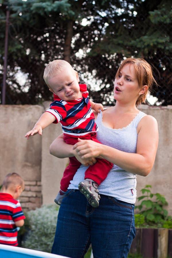 женщина малыша удерживания мальчика плача сварливая outdoors стоковое изображение