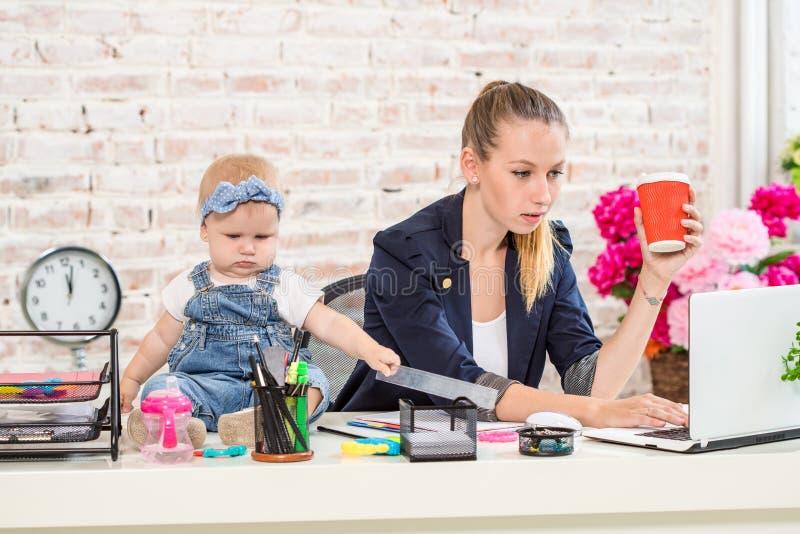 Женщина матери коммерсантки при дочь работая на компьтер-книжке стоковая фотография