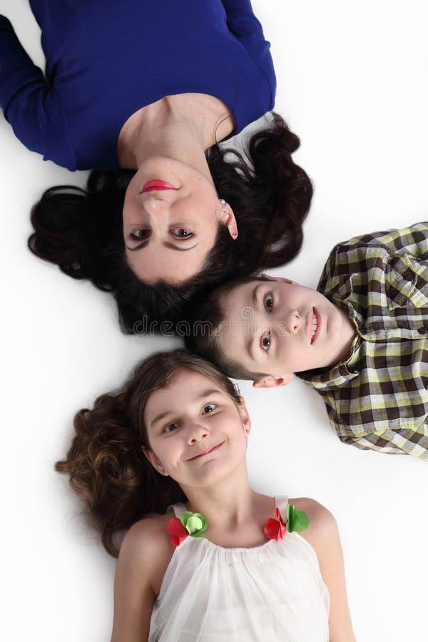 Женщина, мальчик и девушка лежат на поле на сером цвете стоковые фотографии rf
