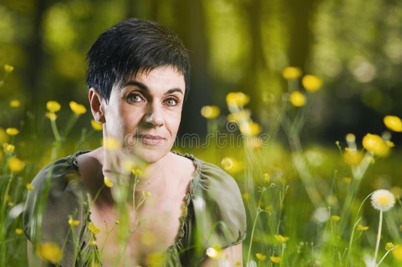 Женщина между цветками стоковая фотография rf