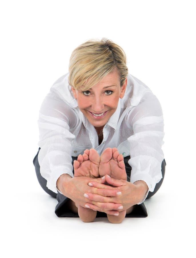 Женщина менеджера делая йогу на белой предпосылке стоковое изображение