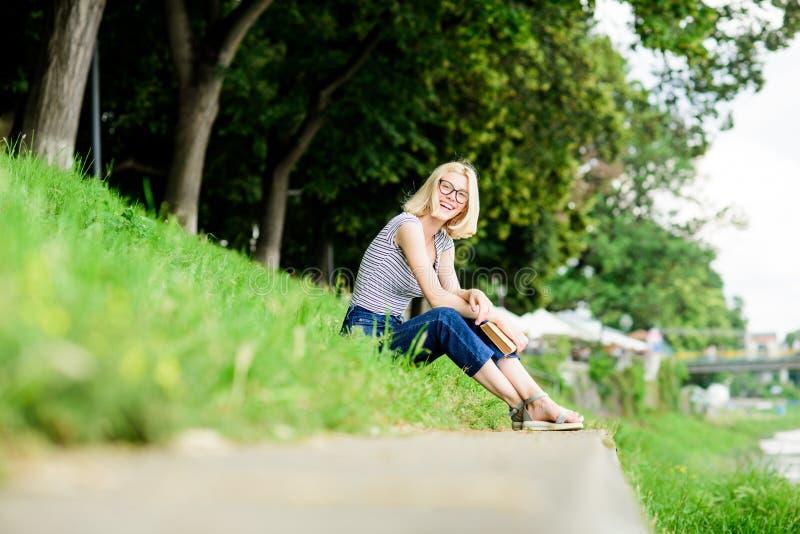 Женщина мечтая о каникулах Литература на летние каникулы Девушка ослабляя на береге реки после рабочего дня Остатки ослабляют стоковое изображение
