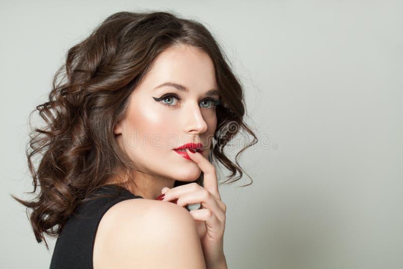 Женщина милого брюнета модельная с макияжем и коричневым курчавым портретом стоковые изображения