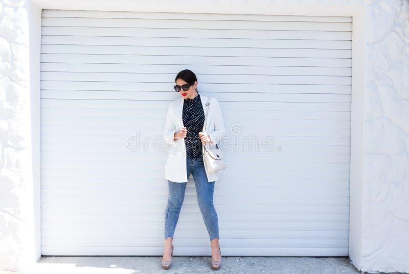 Женщина милой молодой моды чувственная представляя на белой предпосылке стены одетой в обмундировании джинсов стиля и белой куртк стоковое изображение rf
