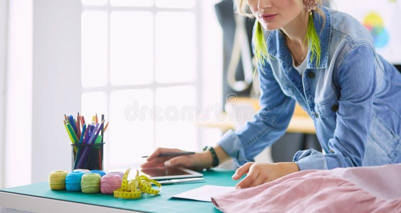 Женщина модельера работая на ее дизайнах в студии стоковое фото rf