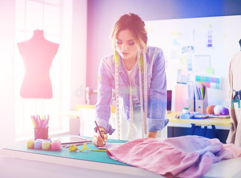 Женщина модельера работая с ipad на ей дизайны в s стоковая фотография