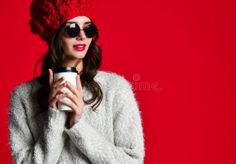 Женщина моды счастливая усмехаясь держит кофейную чашку на красной предпосылке стены стоковые изображения rf