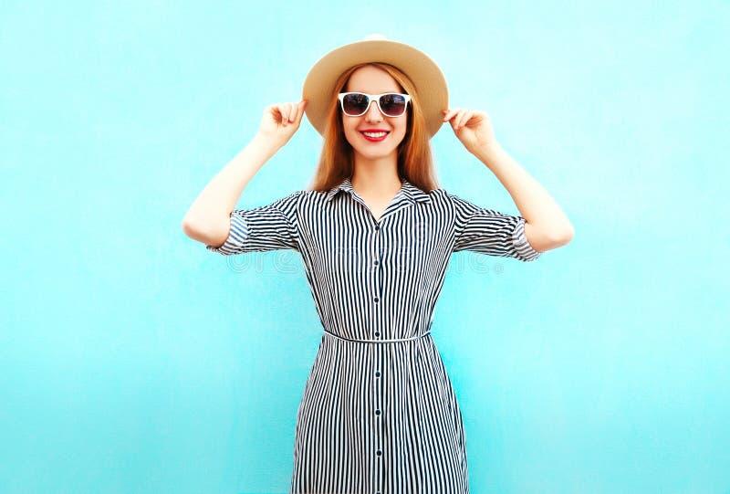 Женщина моды усмехаясь нося striped платье, соломенную шляпу лета стоковая фотография